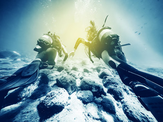 Two divers swimming close to the ocean floor.