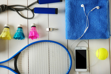 Sport equipment with mobile phone on white wooden background