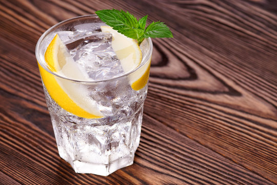 Gin and tonic. Gin tonic with ice in a glass on a textural background.