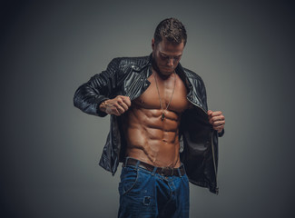 Portrait of athletic male in a jeans and leather jacket.
