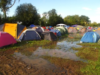 summer music festival flooded campsite muddy tents in England, UK