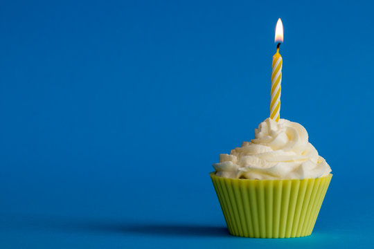 yellow birthday cupcake with candle and blue background
