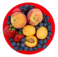 Fresh blueberry, strawberry, peach and apricot on a red plate
