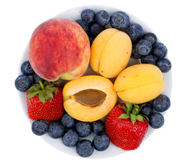 Fresh blueberry, strawberry, peach and apricot on a white plate