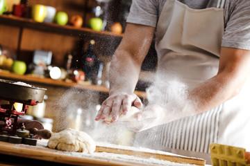 Male baker prepares bread. Male baker slaps on dough. Making bread.