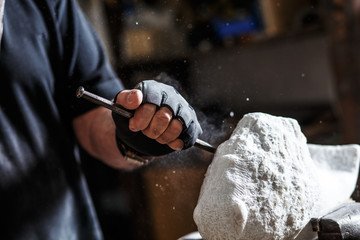 Close up of senior sculptor hands working on his marble sculpture in his workshop with hammer and chisel