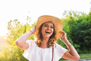 Beach woman laughing having fun in summer vacation holidays. Girl wearing big straw hat