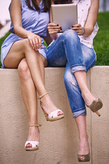 Girls using tablet, sitting outdoors
