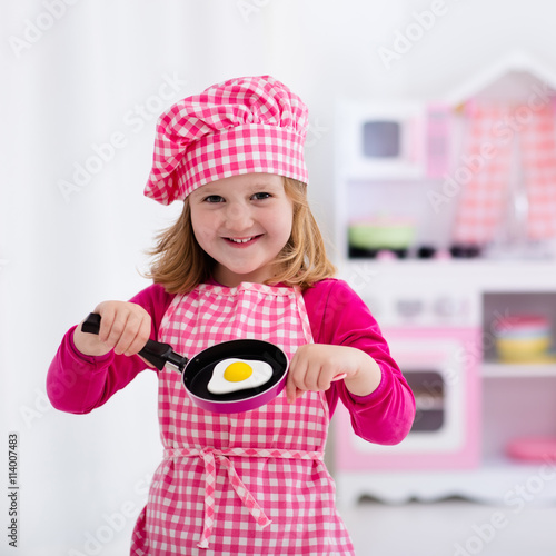 """Little Girl Playing With Toy Kitchen"" Imagens E Fotos De"