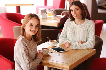 Young happy women talking in cafe