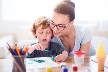 Little boy painting picture for mother