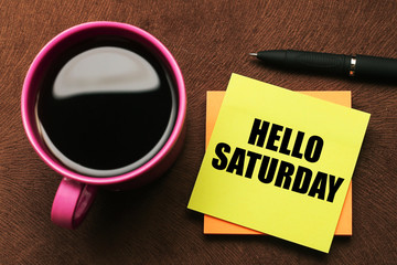 Hello Saturday - text on sticky note with a pen and cup of coffee