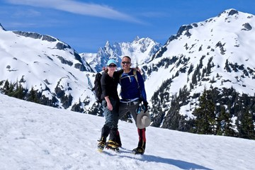 Happy friends hugging on snow covered mountain top. Mount Shuksan, North Cascades National Park, Washington state, USA.
