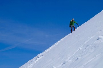 Man climber on snow covered steep mountain slope. Mount Baker wilderness, North Cascades National Park, Washington, USA.