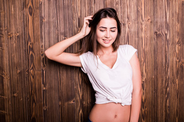 Girl posing against wooden wall