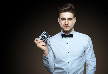 Handsome young man with a camera in his hands. Photographer's work. Festive photo. Photos creativity