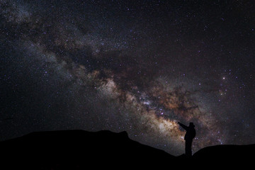 A Man is standing next to the milky way galaxy pointing on a bri