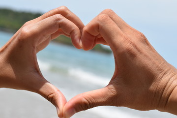 Hands in the shape of a heart on a background of blue sea