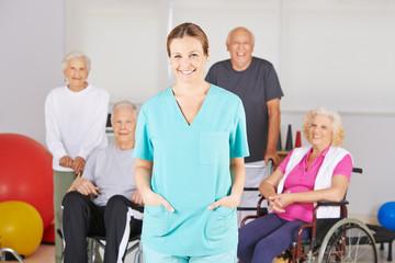 Krankenschwester vor Gruppe Senioren im Pflegeheim