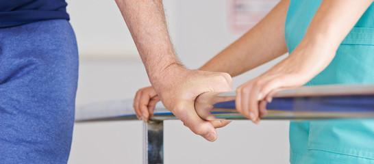 Hand eines Senioren am Geländer bei Physiotherapie
