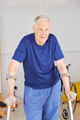 Alter Mann mit Krücken lernt gehen bei Reha