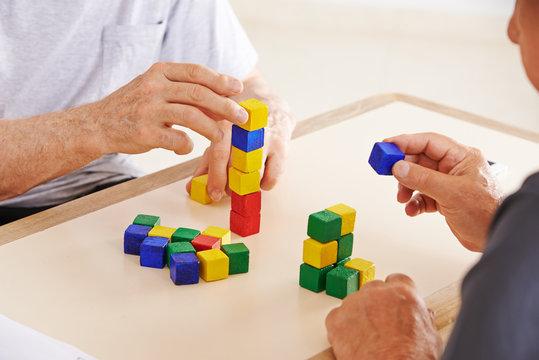 Hände von Senioren mit Demenz bauen Turm