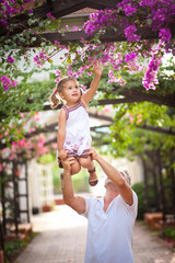 Dad plays and laughs with her baby daughter in blossoming garden