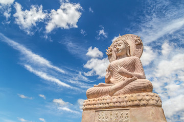Carved sandstone Buddha statue on blue sky background