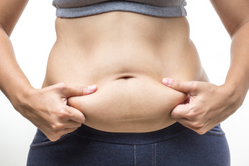 overweight woman with hand holding fat belly