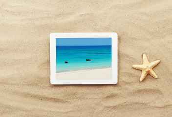 Tablet with photo of the blue sea and two boats