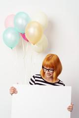 frau zeigt ein hinweisschild mit luftballons