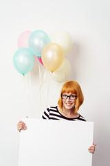 lachende frau mit ballons zeigt ein weißes plakat