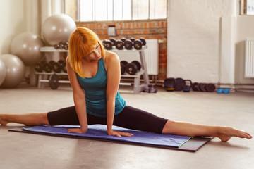 frau im fitness-studio dehnt die beine