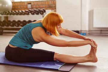 sportliche junge frau dehnt die beine im fitnessstudio