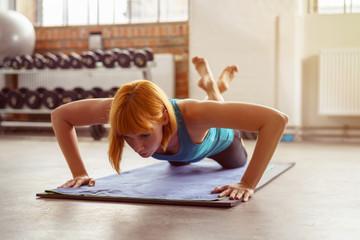frau macht liegestütz im fitness-studio