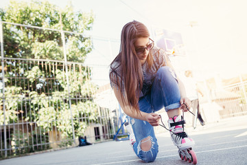 Urban vintage portrait of beautiful and attractive girl with sunglasses putting on her roller skates. Warm summer colors and haze. Strong backlight.