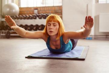 frau trainiert ihren rücken im fitnessstudio