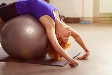 frau dehnt sich über einen ball im fitness-studio