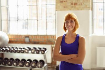 junge frau steht mit verschränkten armen im fitnessstudio