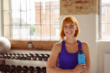lächelnde frau mit wasserflasche im fitnessstudio