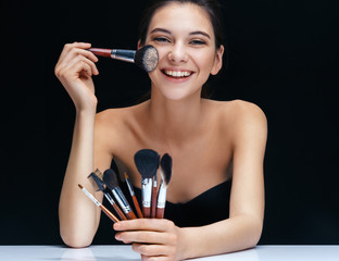 Smiling brunette girl with brushes for make up on black background. Youth and skin care concept
