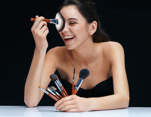 Beautiful woman with make up brushes near her face. Photo laughing girl of European appearance on black background