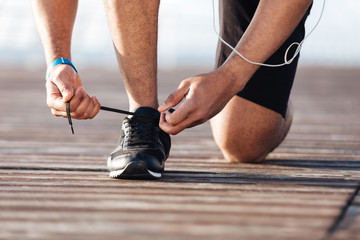 Sportsman laces his sneakers on pier Wall mural