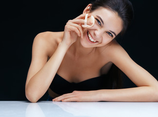 Smiling girl applying powder. Portrait of brunette woman toothy smile on black background. Youth and skin care concept
