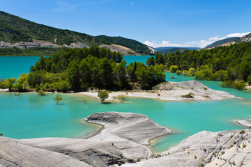 travel to turquoise limestone lake of yesa in blue sky, spain