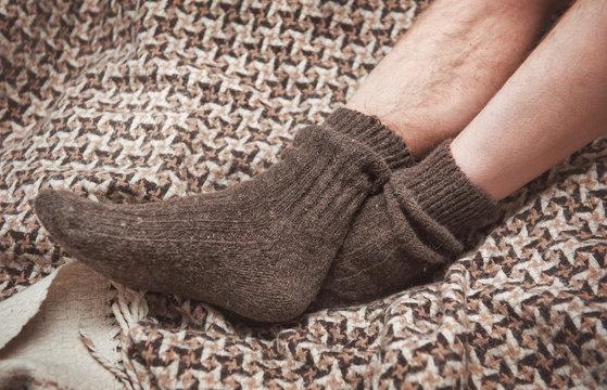 Man feet on woolen plaid in woolen socks