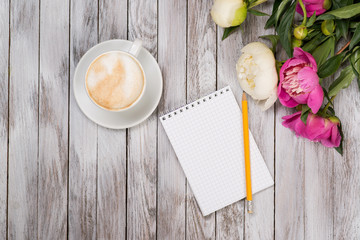 Notebook with a pencil next to coffee and peonies flowers on wooden background. Top view.