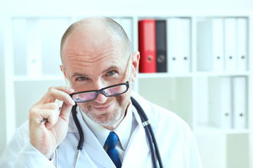 Old male doctor looks into the camera and smiling while holding glasses in hand. Medical care or insurance concept