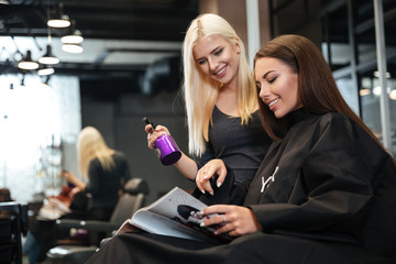 Woman discussing hairstyling with her hairdresser in hairdressing salon