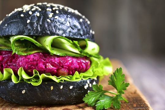 Vegan black burger with beetroot on a cutting board.